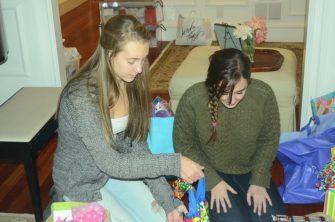 Abby Mills (left) and Julie Waszak prepare presents for disadvantaged children.